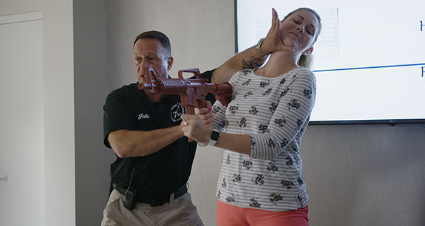 John Nettis from PASS, left, demonstrates fighting techniques July 17 with Amanda Moyer, director of account services at Market Mentors at the Market Mentors office in Springfield, Massachusetts. (Photo: Justin Bedard/Market Mentors LLC via AP)