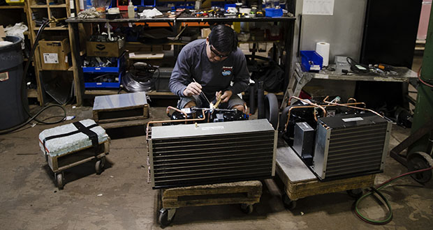 In this October 2018 photo, Minh Pham works on a compressor unit at a commercial refrigeration manufacturing facility in Philadelphia. Small manufacturers and retailers are losing confidence in the national economy yet remain upbeat about their own prospects. (AP file photo)