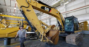 Analysts expect the Caterpillar Inc. to post its first year-over-year decline in quarterly profit since 2016 when it reports results on Wednesday. In this Sept. 18 photo, a Puckett Machinery Co. technician walks past a new heavy duty Caterpillar excavator that awaits modification in Flowood, Mississippi. (AP file photo)