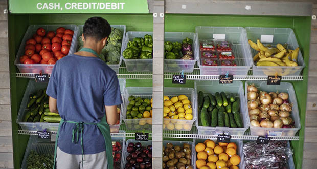 The Consumer Price Index for September showed that food costs edged up a tiny 0.1%, continuing a long string of modest increases. In this Aug. 21 photo, a worker stocks a produce stand at a metro station in Atlanta. (AP Photo: David Goldman)