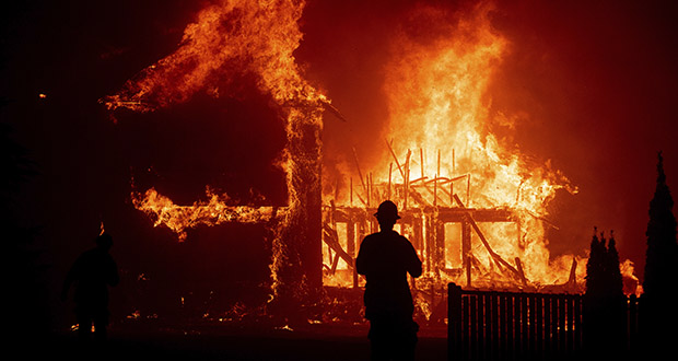In the context of California wildfires or other natural disasters, the endowment effect says that someone who owns a damaged or destroyed home will have a strong preference for rebuilding over moving somewhere else. In this Nov. 8, 2018, photo, a home burns as a wildfire called the Camp Fire rages through Paradise, California. (AP file photo)