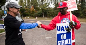 Picketing United Auto Workers Richard Rivera, left, and Will Myatt react Wednesday to news of a tentative contract agreement with General Motors, in Langhorne, Pennsylvania. (AP Photo: Matt Rourke)