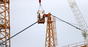 Workers in a bucket hoisted by a crane Friday begin the process of preparing the two unstable cranes for implosion at the collapse site of the Hard Rock Hotel, which underwent a partial, major collapse while under construction Saturday, Oct. 12. (AP Photo: Gerald Herbert)