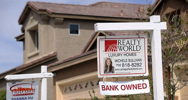 """A """"bank owned"""" sign sits outside a foreclosed home April 15, 2010, in Las Vegas. Even a decade after a crash that left millions jobless and evicted from their homes, the same bankers who created pools of risky loans continue to benefit. (Bloomberg file photo)"""