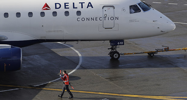 Delta CEO Ed Bastian says Delta is getting a boost from strong spending by consumers, which he expects to spill into 2020. In this Feb. 5 photo, a ramp worker guides a Delta Air Lines plane at Seattle-Tacoma International Airport in Seattle. (AP file photo)