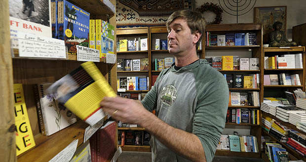 Pete Mulvihill looks over one of the recommended books on display at his Browser Books store Dec. 4 that he recently opened in San Francisco. Mulvihill has felt optimistic enough about being an independent bookseller that he bought a third store within the past two months. (AP Photo: Eric Risberg)