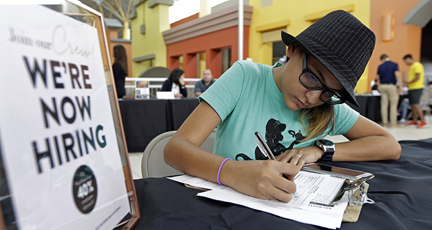 In this Tuesday, Oct. 3, 2017, file photo, Job seeker Alejandra Bastidas fills out an application at a job fair,  at Dolphin Mall in Sweetwater, Fla. (AP Photo/Alan Diaz, File)