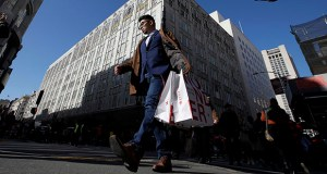 In this Nov. 29, 2019, file photo a man carries shopping bags across the street from a Macy's store in San Francisco. (AP Photo/Jeff Chiu, File)