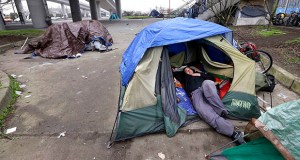In this Feb. 9, 2016 file photo, a man lies in a tent with others camped nearby under and near an overpass in Seattle. (AP Photo/Elaine Thompson, File)