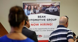 In this Sept. 18, 2019, file photo people stand in line to inquire about jobs available at the Bean Automotive Group during a job fair designed for people fifty years or older in Miami. (AP Photo/Lynne Sladky, File)
