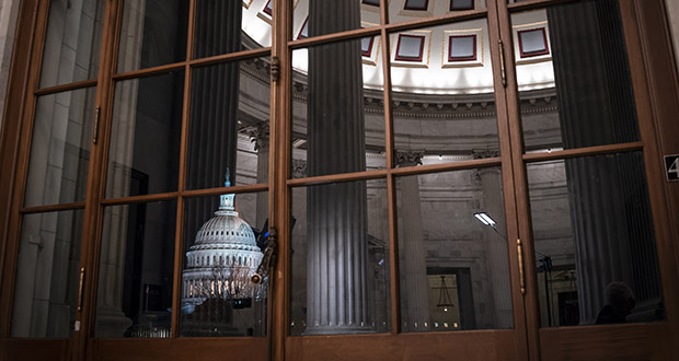 In this Jan. 29, 2020, file photo the Capitol is seen amid reflections of the Russell Senate Office Building in Washington. On Wednesday, Feb. 12, the Treasury Department releases federal budget data for January. (AP Photo/J. Scott Applewhite, File)