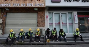 """Workers take a rest Sunday near the closed restaurant and bank in Wuhan in central China's Hubei province. Warning that China's virus epidemic is """"still grim and complex,"""" President Xi Jinping called Sunday for more efforts to stop the outbreak, revive industry and prevent the disease from disrupting spring planting of crops. (Photo: Chinatopix via AP)"""