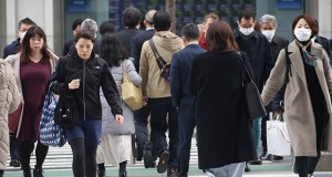 People walk on street in Tokyo on Monday. The Japanese economy shrank at an annual pace of 6.3% in the October-December period. (AP photo)