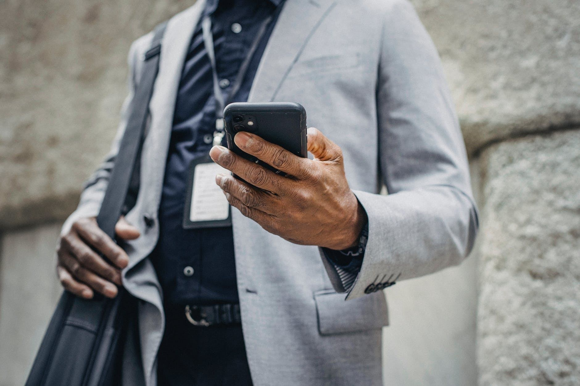 crop faceless businessman browsing smartphone on street