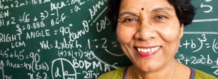 Cheerful Senior Indian Mathematics Teacher in a Classroom