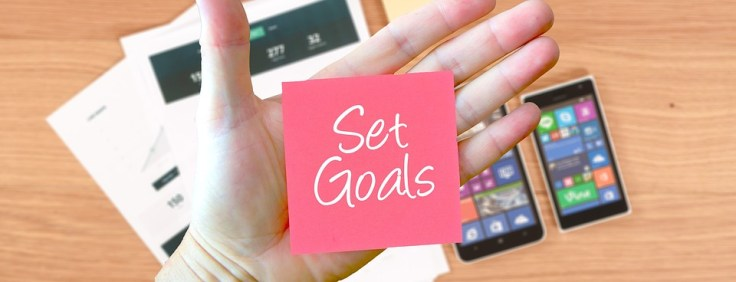 "Hand with a pink sticky note that says ""set goals"""