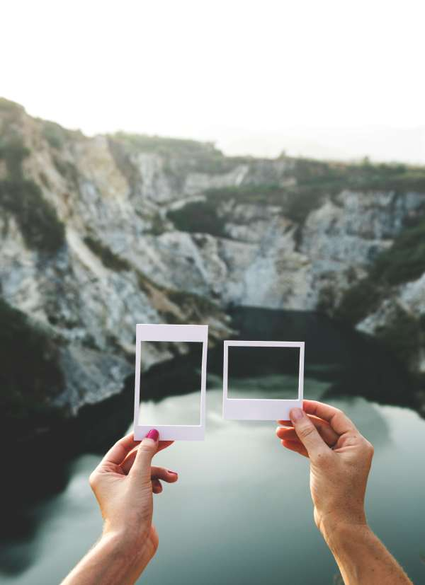 two hands holding up different sized pictures frames in front of mountain