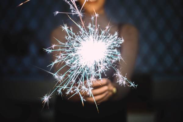 woman holding sparkler in front of her with two hands