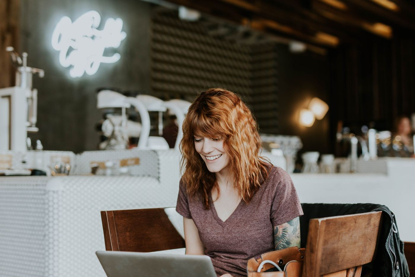 red headed woman at a coffee shop on a laptop