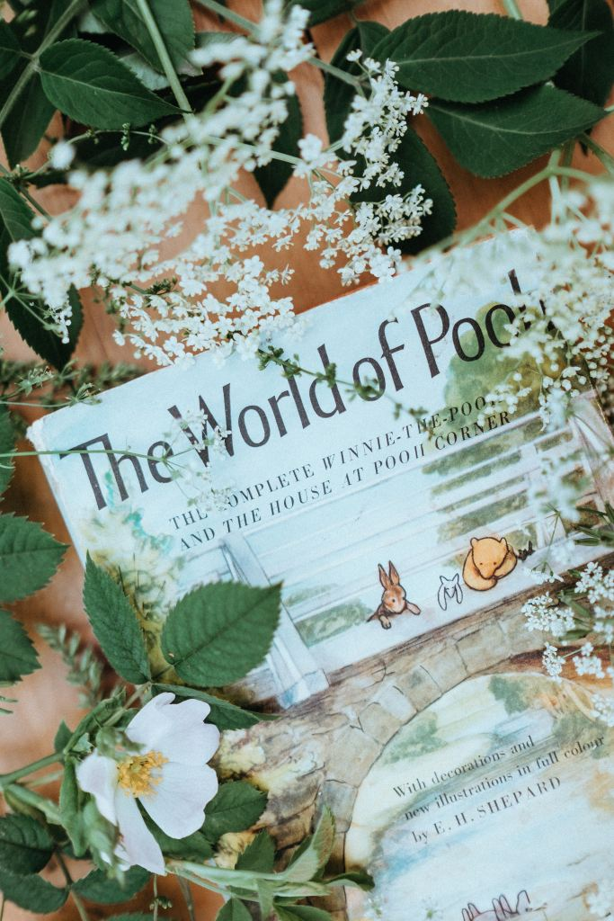 The World of Pooh Book surrounded by flowers