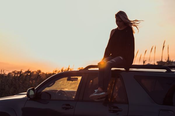 lifestyle design woman sitting on car at sunset