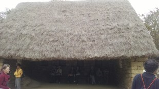A restored wayrona, a three sided structure with a thatched roof.