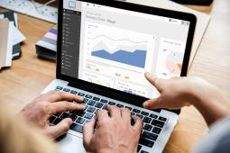 Finger pointing to business chart on macbook