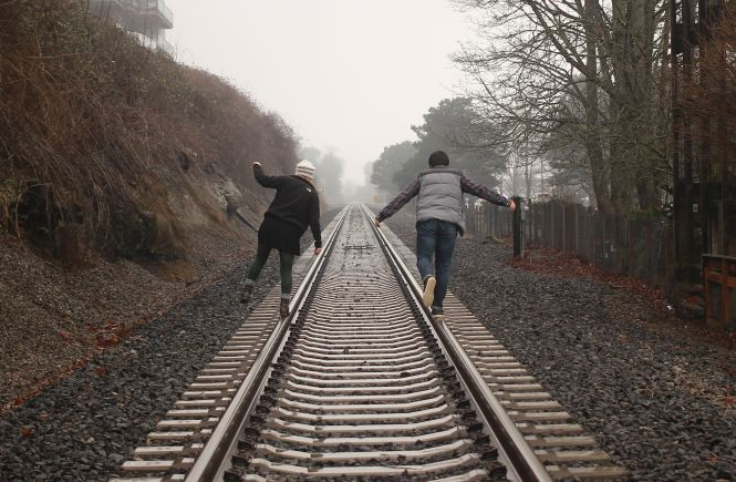 A couple balancing on train tracks