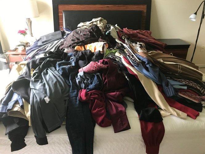 a huge pile of clothes on the bed