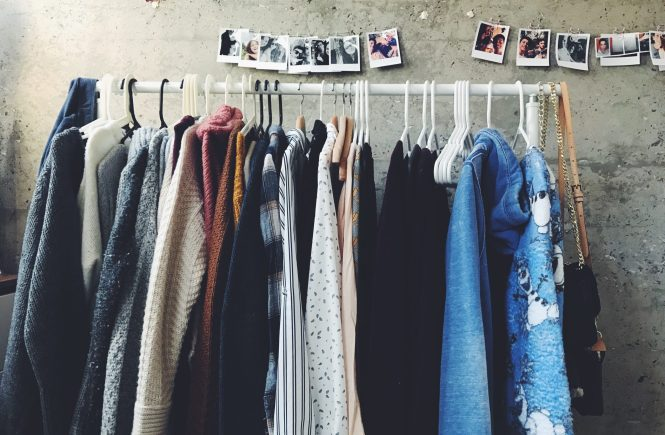 clothes on a hangar with pictures hung on the wall