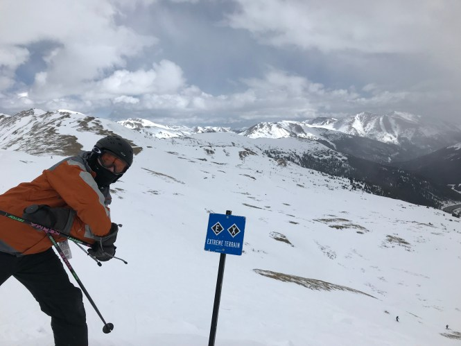 Mr. Mechanic in front of extreme terrain sign skiing in the mountains