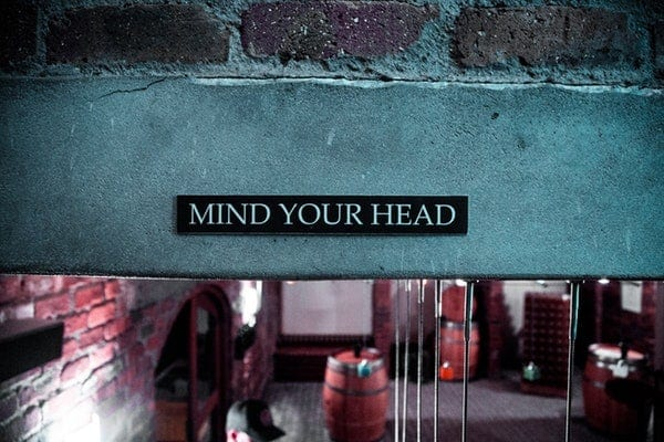 A sign in a restaurant that reads, mind your head