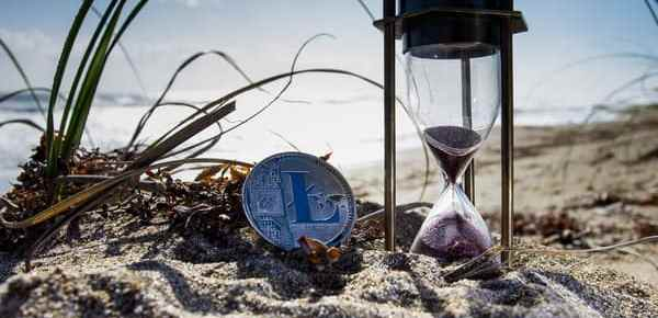 A coin and sand timer on a beach signifying to just start investing as a young debt-free family
