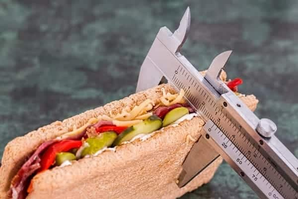 Photo of measuring tool on a sandwich to show the importance of tracking in fitness and personal finance