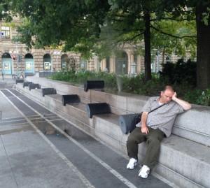 Sleeping man next to water fountain