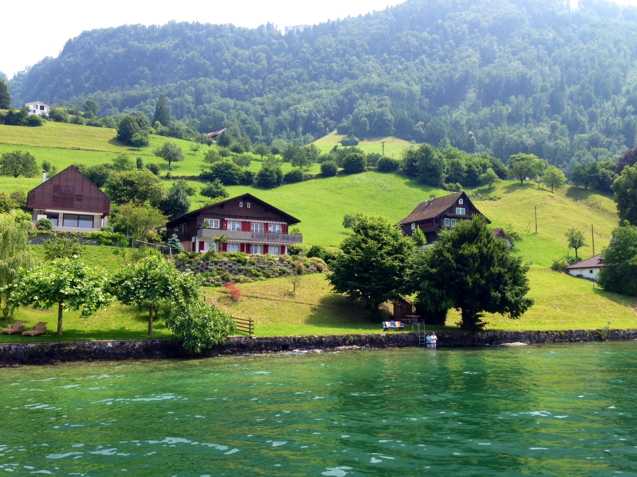 A couple stepping into Lake Lucern from their house - The Key To Taking A Guilt-Free Expensive Vacation