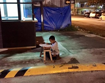 Homeless Philippino boy studying under a McDonald's light