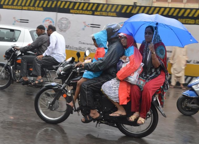 A family cover themselves to avoid rain in Hyderabad on Saturday. Pic:Style photo service.