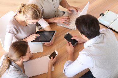ludzie przy biurku z telefonami i komputerami