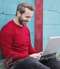 Uśmiechnięty mężczyzna pracuje z laptopem na kolanach