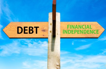 Wooden signpost with two opposite arrows over clear blue sky, Debt versus Financial Independence messages, Personal Finance conceptual image