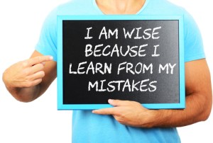 Man holding blackboard in hands and pointing the word I AM WISE BECAUSE I LEARN FROM MY MISTAKES