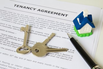 Tenancy agreement, key and pen with symbolic miniature house