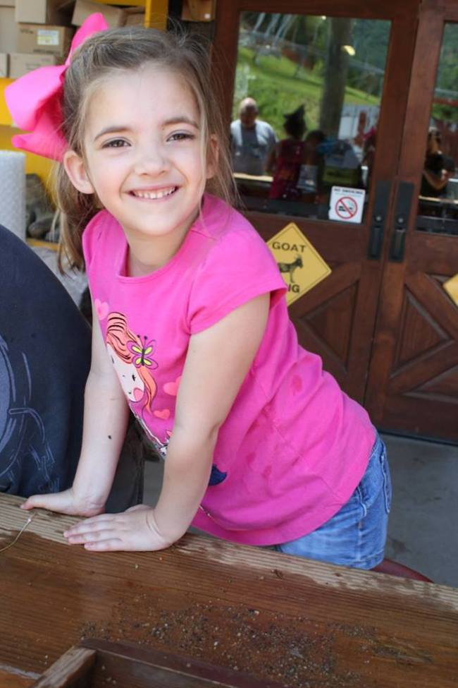 little girl stops to smile for a picture while gem mining during a weekend in Pigeon Forge, Tennessee.