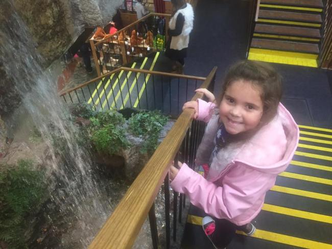 girl beside the waterfall at the Smoky Mountain Works store in Sevierville, TN