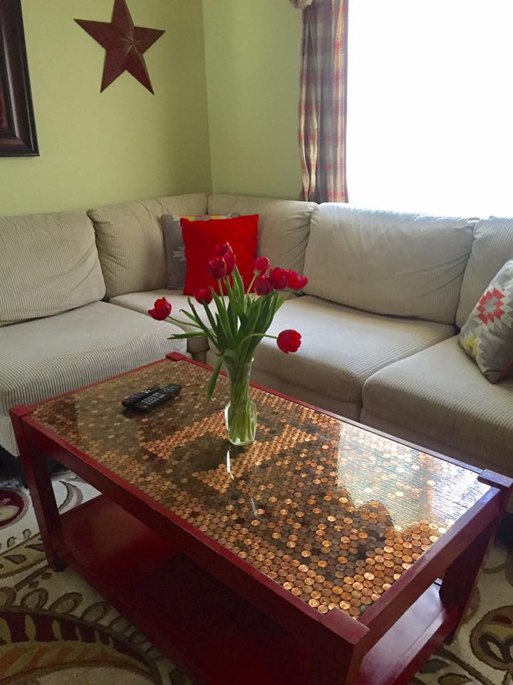 The coffee table after pennies were added to the top.
