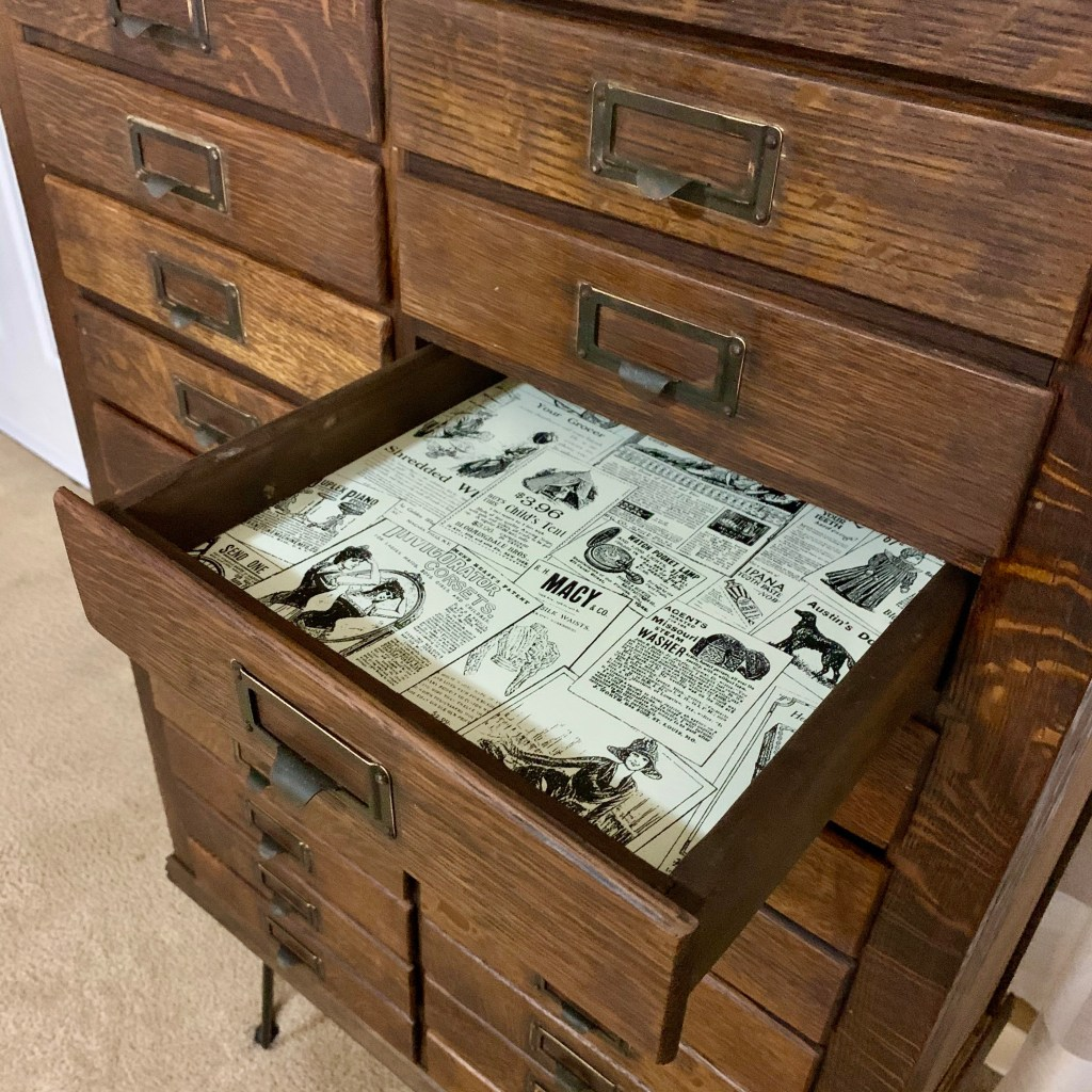 We used vintage newspaper peel and stick wallpaper to line the drawers.