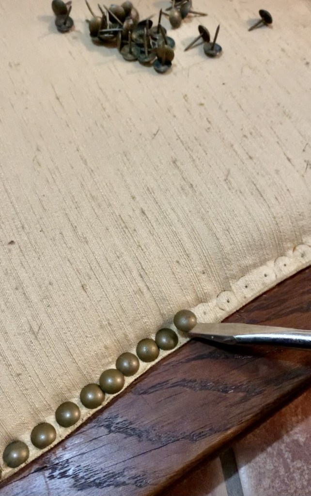 When we refurbish antique bed we take the tacks out with a flat head screwdriver.