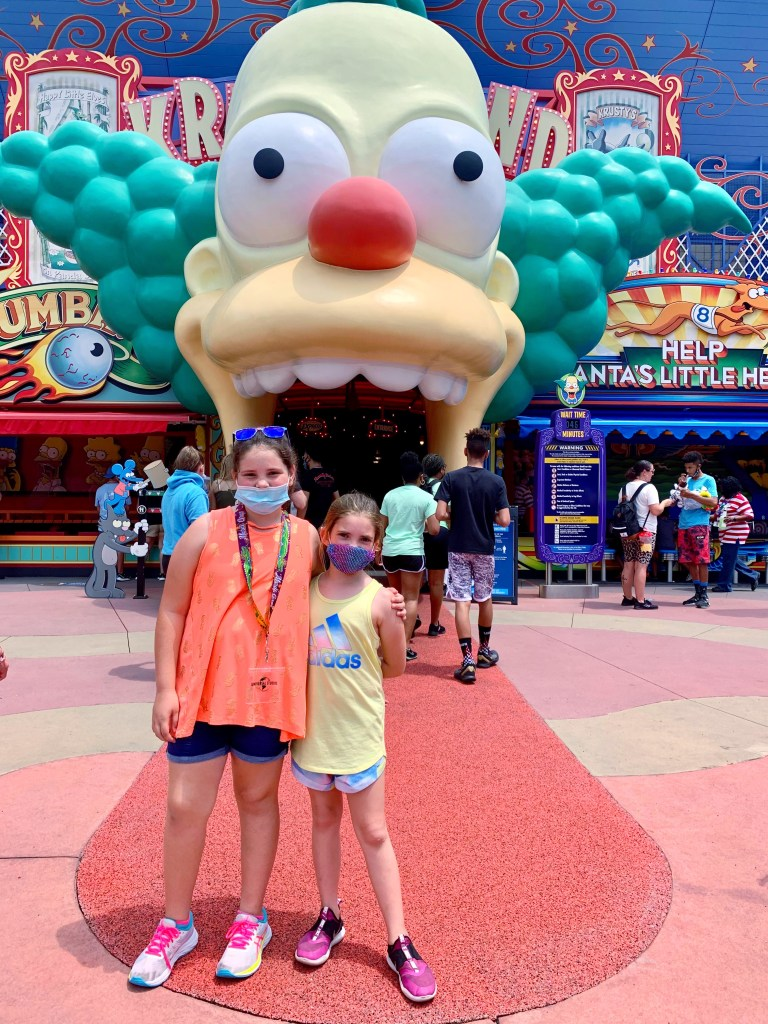 Girls standing in front of The Simpson ride at Universal Orlando.