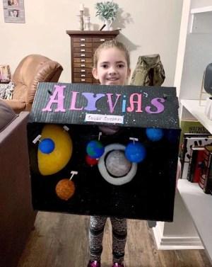Taking her model solar system to school!